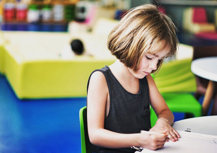 A child writing - image for the article Is CBD Safe for Children